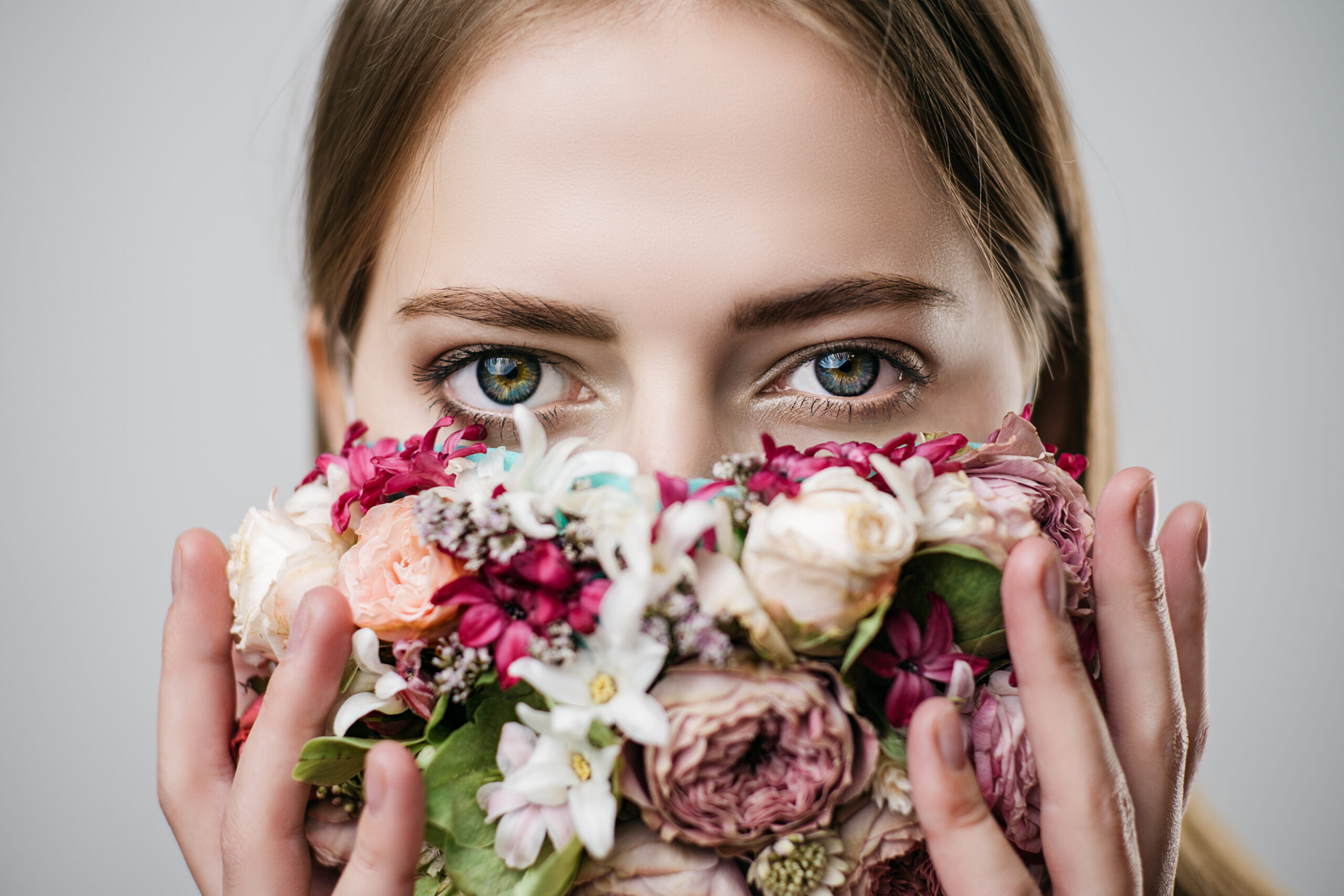 Beautiful girl with a mask of flowers